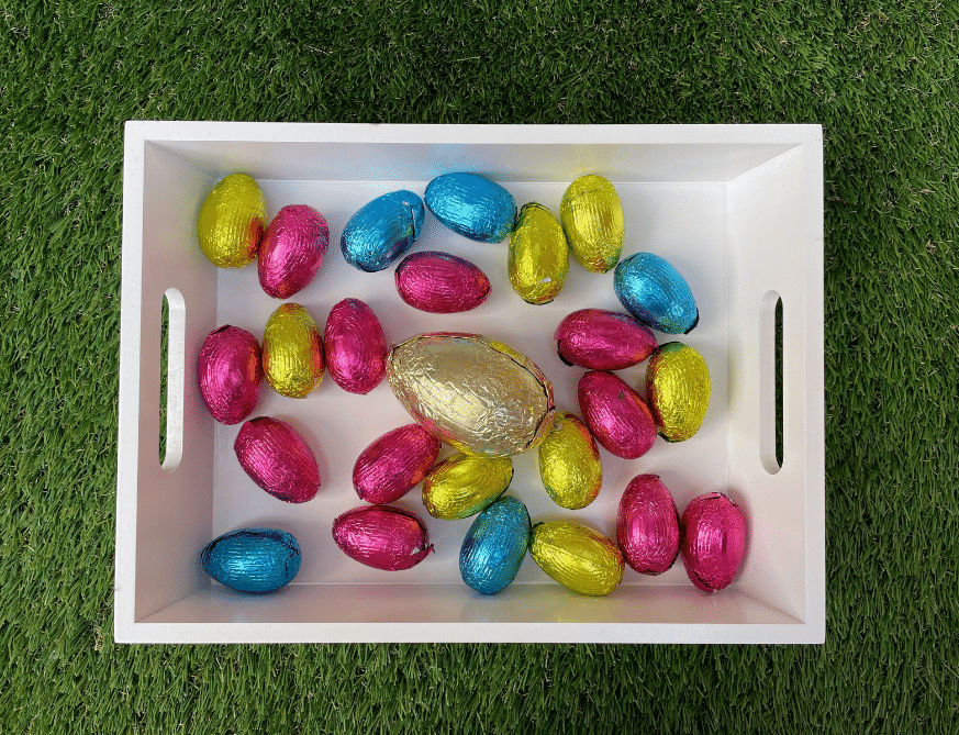 A white tray is resting on grass. Inside the tray are lots of different coloured small easter eggs in pink, yellow and blue. There is one larger gold egg