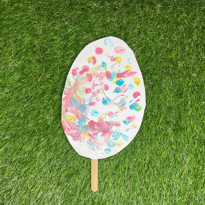 On a grass surface is an egg cut out of paper. It has red, yellow and blue fingerprints all over it and there is a wooden lolly stick poking out of the bottom
