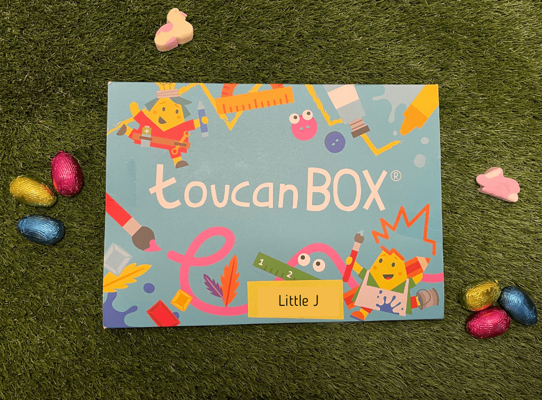 The toucanBox is resting on a grass surface. It is blue with white writing and lots of craft pictures all over it in pink, yellow, orange, red, green, white and grey. It has Little J written on the front in black ink on yellow paper. There are some small pink, gold and blue easter eggs resting next to the box and a duck and rabbit made out of marshmallow in pink, white and yellow.