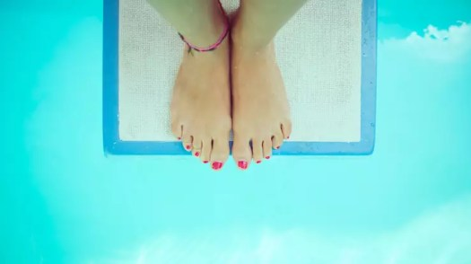 A girl with pink tow nail polish stands on a springboard over turquoise water   Weight Loss and the Waiting Trap   Progress iOS app