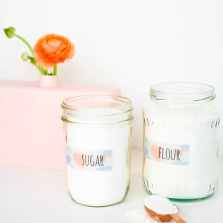 Watercolor Pantry Labels on two mason jars filled with flour and sugar with a tablespoon of flour on the counter and a flower and vase in the background