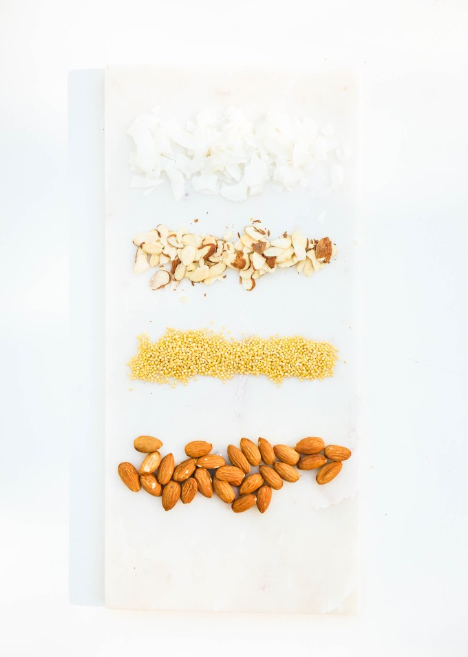 ingredients for homemade almond coconut kind bars on marble slab, almonds, coconut, puffed rice millet