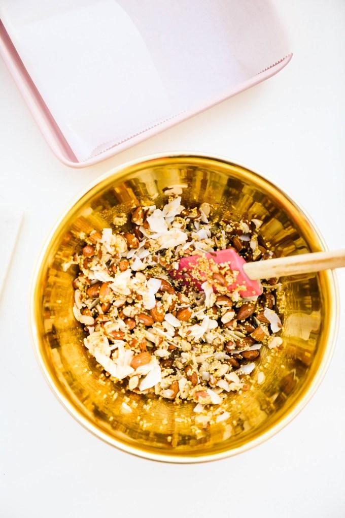 granola bar ingredients in gold mixing bowl