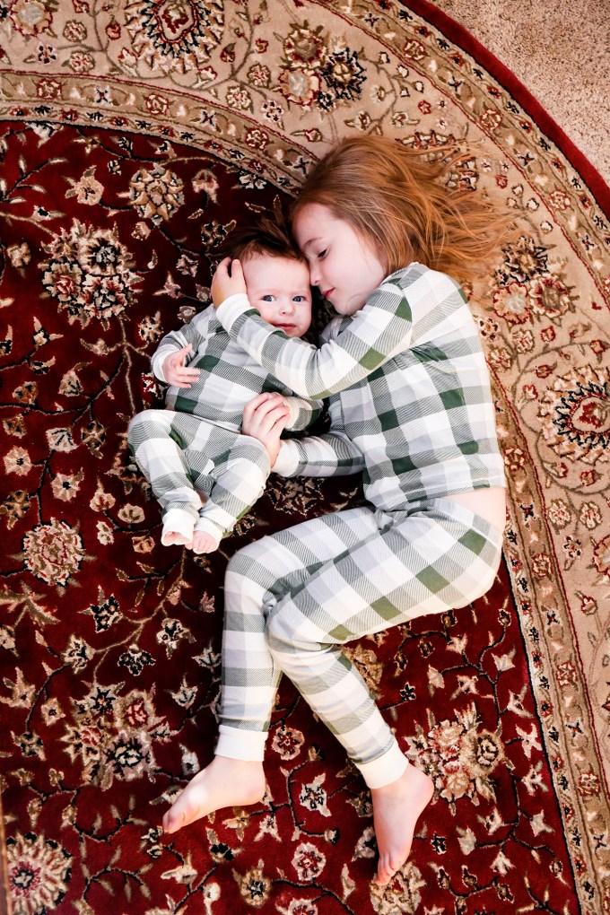 sisters in plaid pajamas on rug
