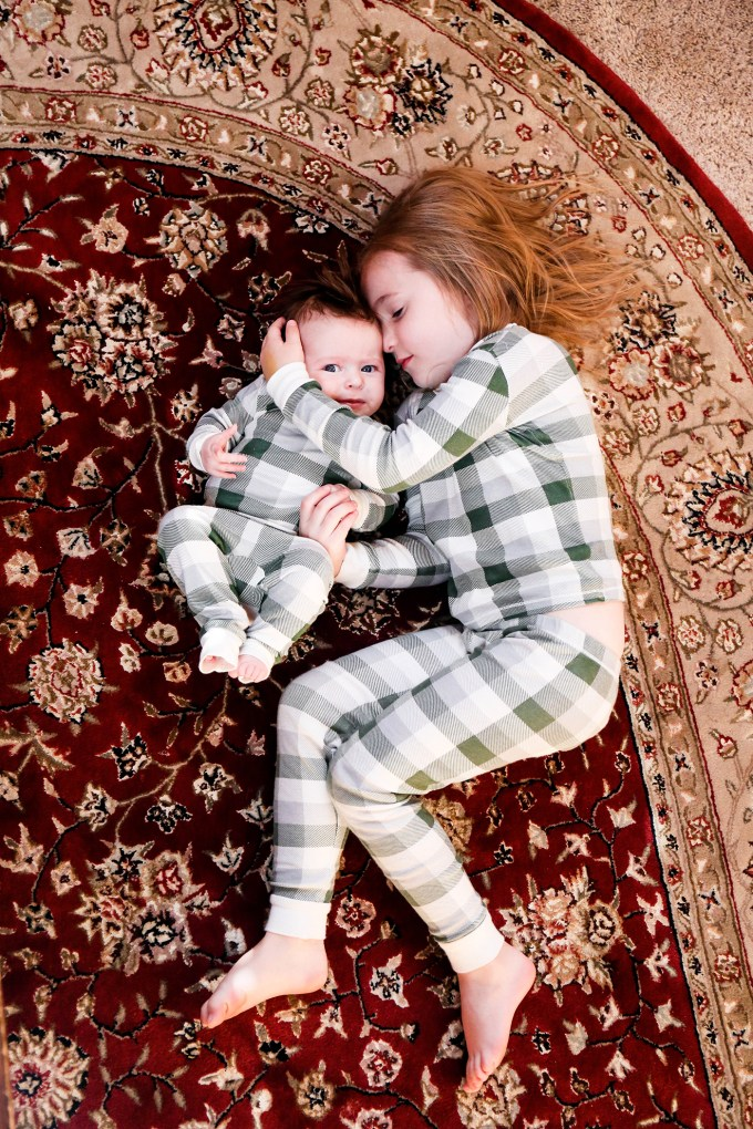sisters in plaid pajamas on rug
