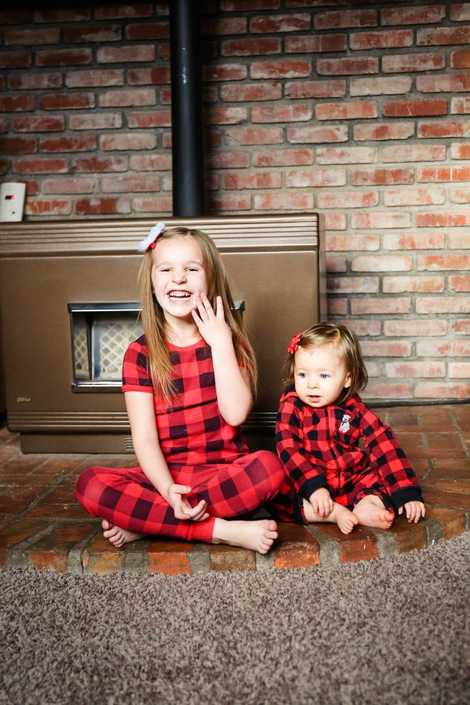 sisters in plaid pajamas in front of stove