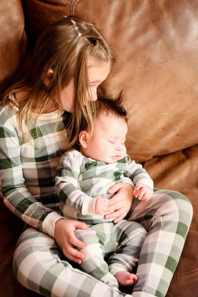 sisters in plaid pajamas on couch