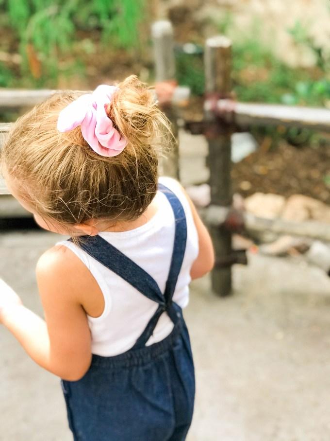 backside of denim overalls on little girl