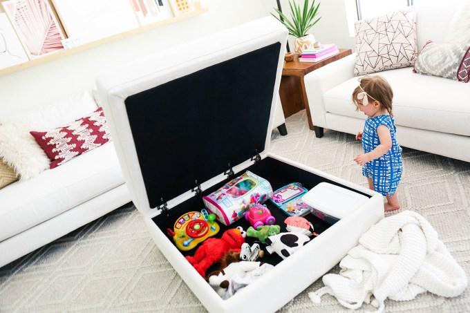 baby surprised by hidden toy storage in furniture
