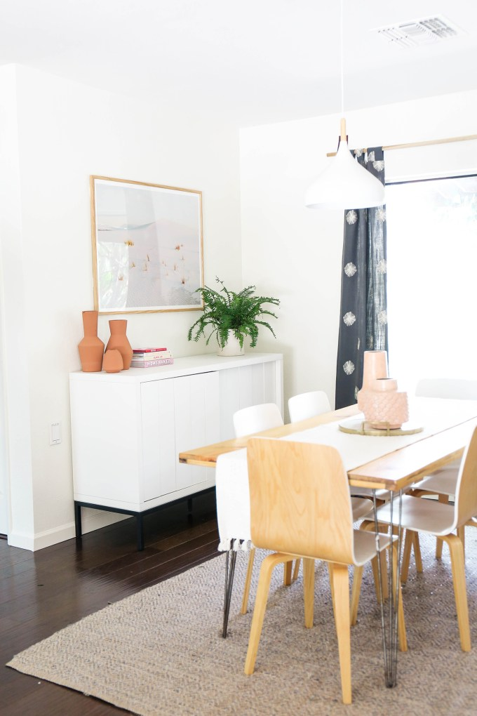 dining room setup with sideboard, table, and curtains