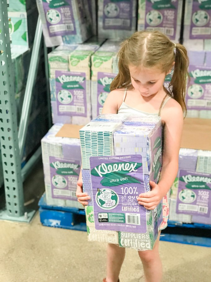 little girl holding kleenex tissues at costco