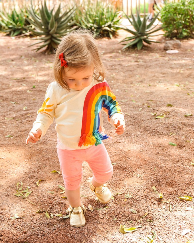 little toddler girl in rainbow sweater