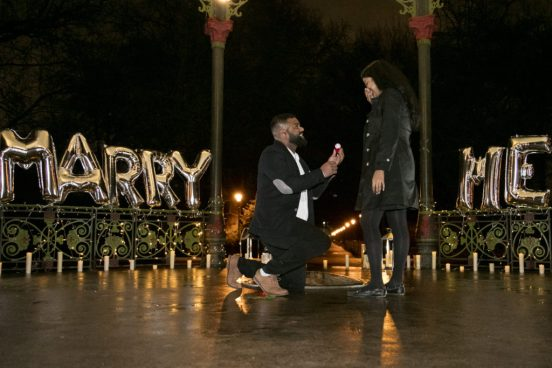 man on one knee proposing to his girlfriend surrounded by foil balloons spelling out 'Marry Me'