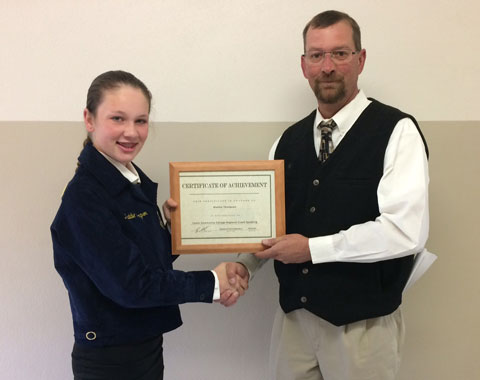 Greg Cash presents the first place certificate to Wiley's Maddie Thompson after competition on Wednesday.