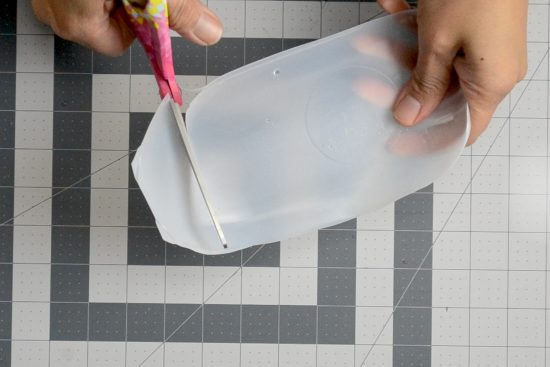 A person cutting a piece of plastic with a pair of scissors.
