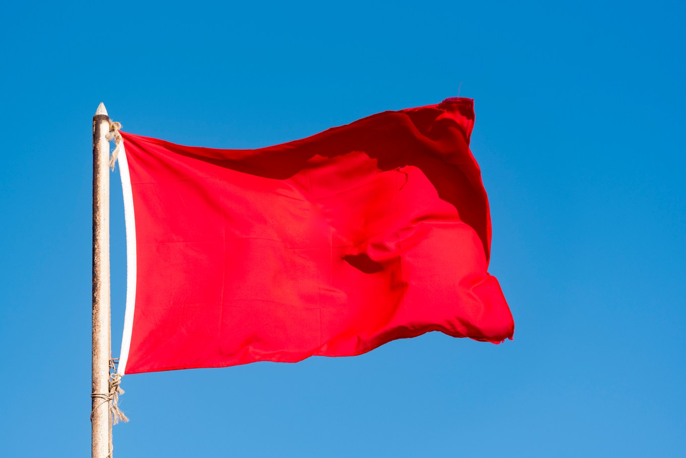 Old red flag and blue sky, red banner waving against blue sky