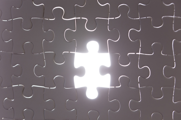 Unfinished white jigsaw puzzle pieces. One missing jigsaw piece on white back light background