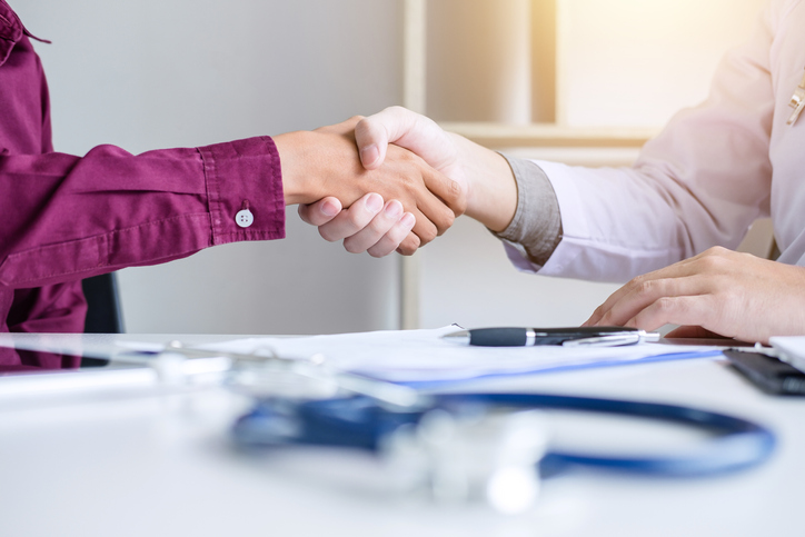 Professional Male doctor in white coat shaking hand with female patient after successful recommend treatment methods, Medicine and health care concept