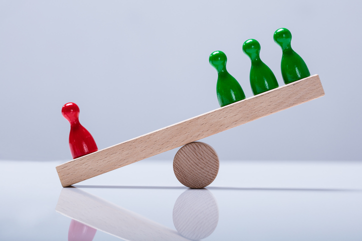 Pawns Figures On Wooden Seesaw