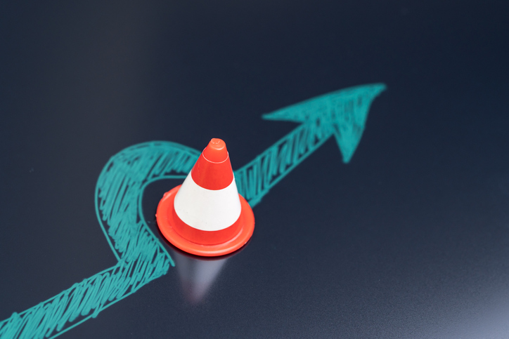 Chalk drawing arrow turn or break through road block traffic pylon on dark blackboard using as obstacle, solution for business problem or break through to success concept