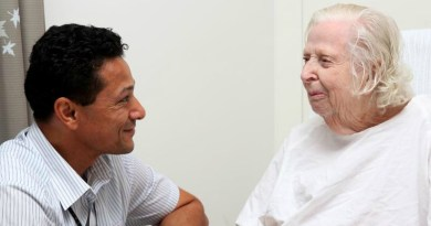 Nursing unit manager Darryl Peterson speaks with patient Norma Ab
