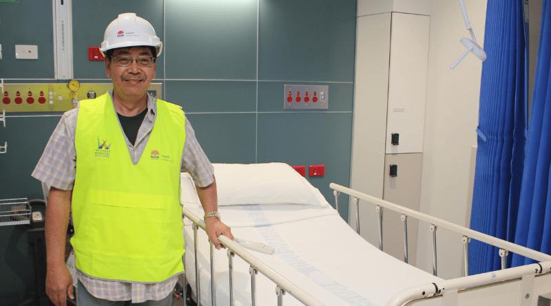 Man in helmet and hi-vis vest stands next to patient bed