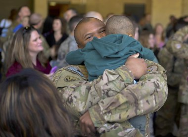 Staff Sgt. Kenneth Redmon, an armament systems craftsman with the 1st Special Operations Aircraft Maintenance Squadron, reunites with his son during an Operation Homecoming at the Deployment Control Center on Hurlburt Field, Fla., Jan 13, 2016. Operation Homecoming brought approximately 80 Airmen home from their deployment overseas. (U.S. Air Force photo by Senior Airman Ryan Conroy)