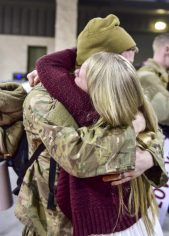 Senior Airman Bryce Evans, a maintenance scheduler with the 1st Special Operations Maintenance Group, reunites with his wife during Operation Homecoming at Hurlburt Field, Fla., Feb. 7, 2016. Operation Homecoming welcomed 106 Airmen home from their deployment overseas. (U.S. Air Force photo by Senior Airman Jeff Parkinson)