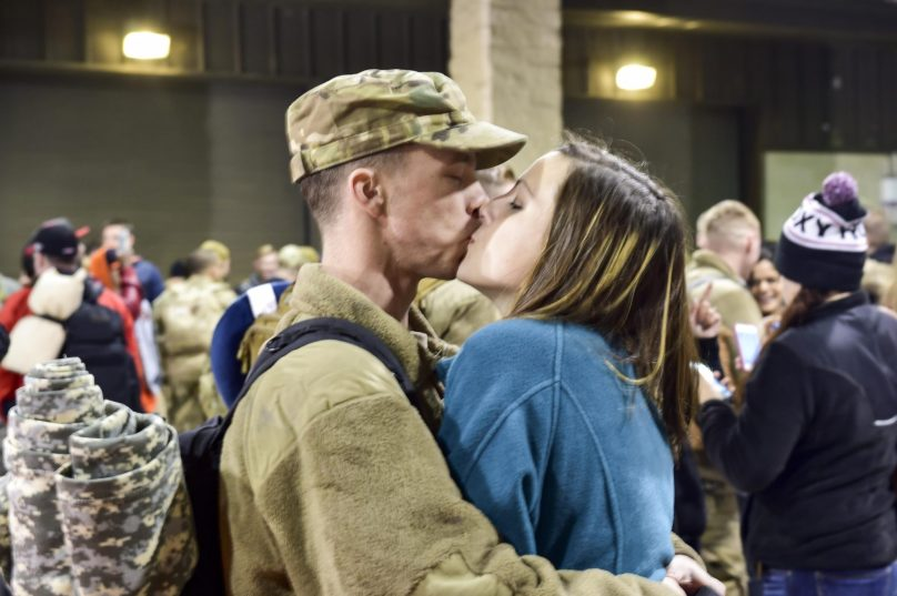 Airman 1st Class Martin Henry, a combat aircraft ground equipment team apprentice with the 1st Special Operations Maintenance Squadron, kisses his wife during Operation Homecoming at Hurlburt Field, Fla., Feb. 7. 2016. Operation Homecoming welcomed 106 Airmen home from their deployment overseas. (U.S. Air Force photo by Senior Airman Jeff Parkinson)