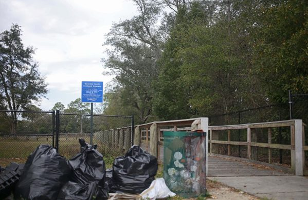 Bags of trash and debris have been left to collect outside the entrance to the Southwest Greenway in Escambia County for several weeks.