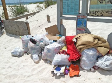 In a provided photo, trash is left at the entrance to the Perdido Key area of Gulf Islands National Seashore.