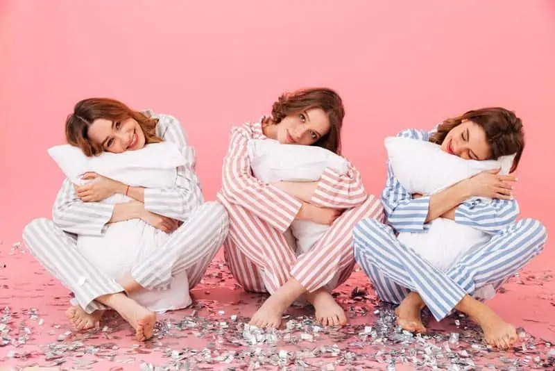 3 girls dressed in striped pyjamas holding pillows
