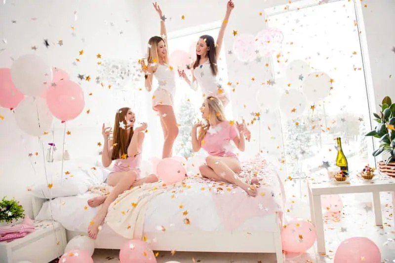 A slumber party with four girls on a bed with balloons and confetti