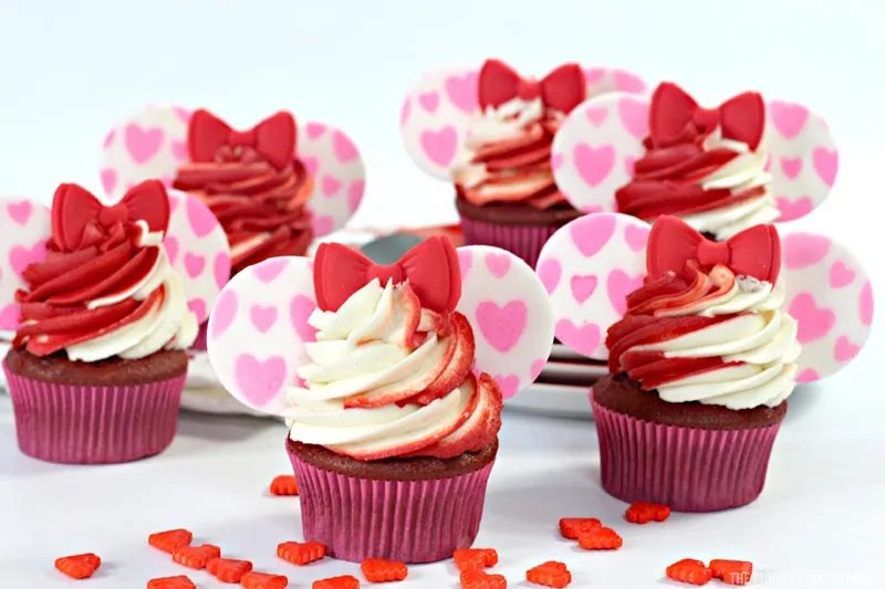 6 Minnie Mouse cupcakes with heart sprinkles around them