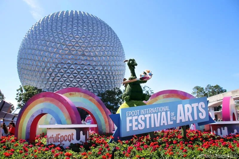 Epcot Festival of the Arts 2019 - A topiary of Figment holding an artist's palette and paintbrush, surrounded by rainbows and the FotA sign, with Spaceship Earth in the background.