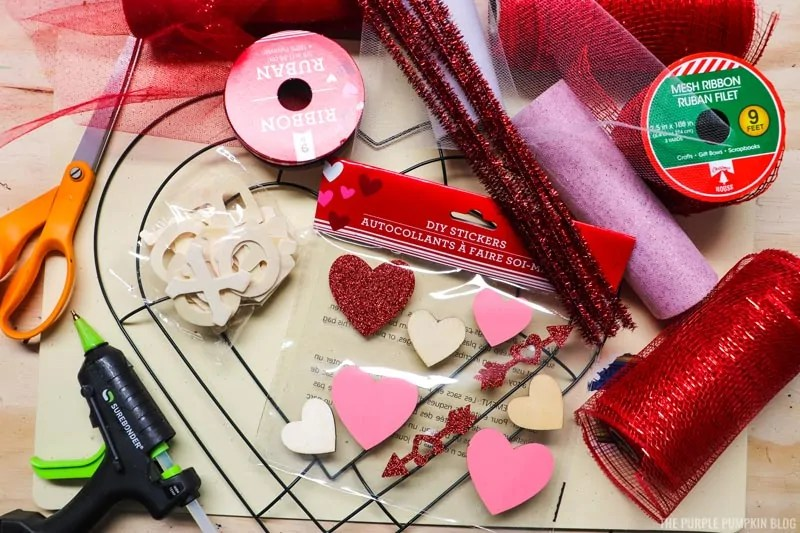 Valentine Wreath supplies including red deco mesh, sparkle mesh, deco ribbon, heart shaped embellishments, a glue gun, scissors, pipe cleaners and a wire heart-shaped wreath form