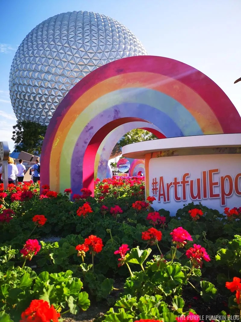 Spaceship Earth with a rainbow in front and a sign saying #ArtfulEpcot