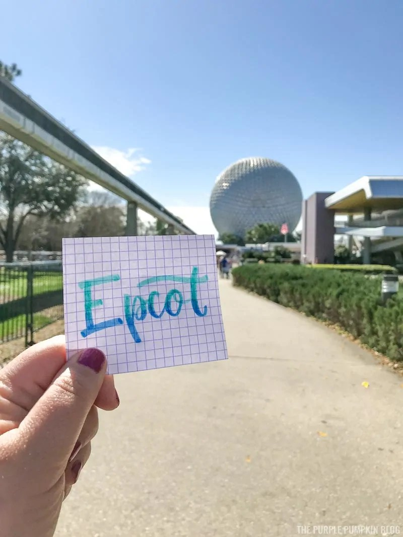 "A piece of paper with the word ""Epcot"" handlettered on in blue with Spaceship Earth in the background."