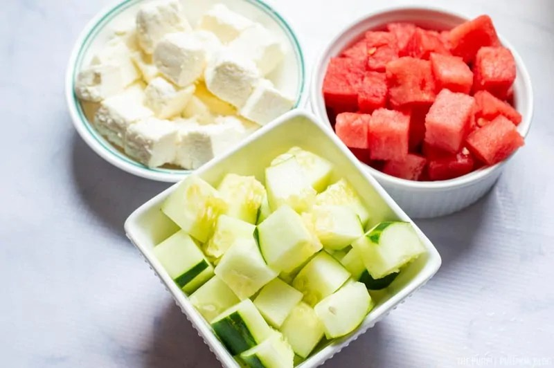 Cubes of feta, watermelon and cucumber in bowls.