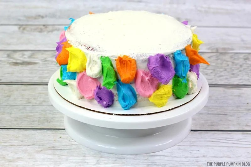 Blobs of colored icing around cake