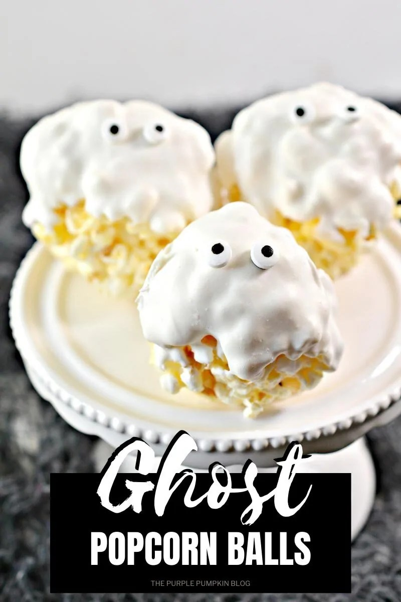 "A cake plate with 3 popcorn balls dipped in white chocolate and topped with candy eyeballs. Text overlay says""Ghost Popcorn Balls"" Similar photos of the recipe/dish from various angles are used throughout and with different text overlay unless otherwise described."
