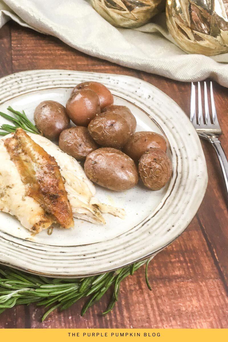 Roasted Lemon Pepper Chicken & Potatoes Recipe - a plate of sliced chicken served with potatoes. The white plate is sat on a wooden table with a fork to the right.