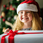 little girl smiling while receiving christmas gift as in the best christmas gift ideas