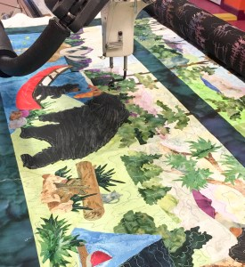 Wilderness applique quilt being quilted on the longarm