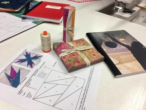 Desktop view of supplies for paper piecing project, pattern, fabric, thread