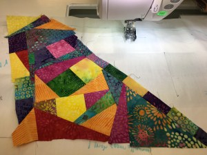 a mosaic of fabric scraps sewn together using a foundation piecing method to make a larger piece of fabric