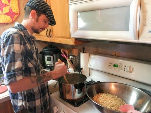 Young man stirring a pot on the stove with a bowl of Rice Krispie cereal in a large bowl next to it
