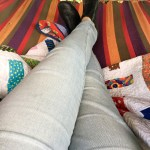 Lady's jeans and shoes laying on a quilt in a hammock
