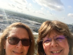 Two smiling friends taking a selfie with the skyline of Houston behind them