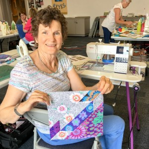 lady holding a quilt block make in the quilting workshop